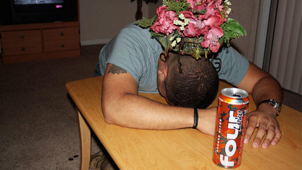 Man passed out with Four Loko in the foreground.