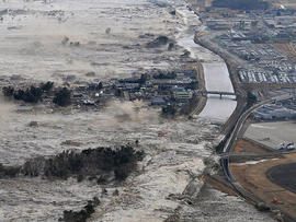 Earthquake-triggered tsunami waves sweep along Iwanuma in northern Japan on March 11, 2022.