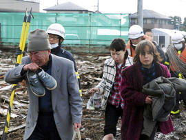 Residents walk through destruction in Sendai