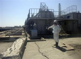 In this Friday, April 1, 2011 photo released by Tokyo Electric Power Co. (TEPCO), a TEPCO employee points at a crack newly discovered in a maintenance pit on the edge of the Fukushima Dai-ichi nuclear nuclear power plant in Okumamachi, Fukushima Prefecture, northeastern Japan. The crack was apparently caused by the March 11 earthquake and may have been leaking since then, said the company's spokesman Osamu Yokokura.