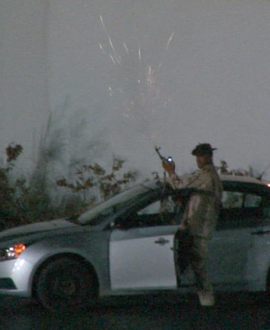 Qaddafi loyalist firing a gun in front of hotel.