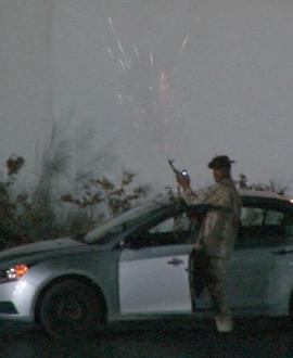 Qaddafi loyalist firing a gun in front of hotel.