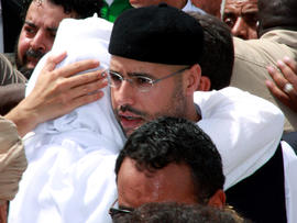 Seif al-Islam Qaddafi, son of embattled Libyan leader Muammar Qaddafi, embraces his brother Mohammad during the funeral of their brother Seif al-Arab Qaddafi at the Al-Hani cemetery in Tripoli, Libya, May 2, 2011, after the 29-year-old was killed along with three of the leader's grandchildren in a NATO airstrike May 1, 2011.