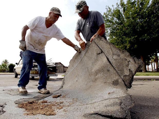 右边的Enemencio Campos和亚利桑那州Eloy的Pedro Lopez,在暴风雨袭击该地区后的第二天,从埃洛伊街的中间捡起屋顶碎片。 Pinal县当局正在评估夏季暴风雨过后Eloy的破坏,留下破坏之路。房屋遭到破坏,屋顶被企业拆除,一所初中学校的部分房屋被遗失。