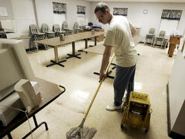 Homeless veteran mops the floor of the dining room at Scott Place shelter, Fairmont, West Virginia