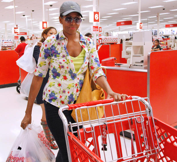 First lady Michelle Obama, wearing a hat and sunglasses, pushes a shopping cart as she carries her purchases at a Target department store in Alexandria, Va., Thursday, Sept. 29, 2011, after doing some shopping.