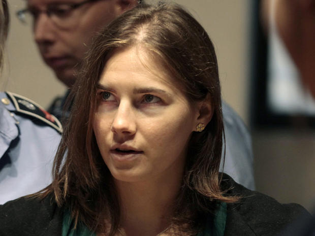 Amanda Knox is escorted as she arrives for an appeal hearing