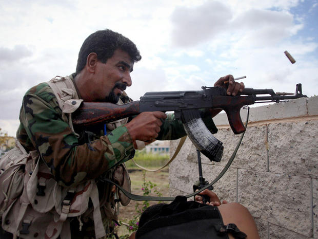 A revolutionary fighter fires at Gadhafi loyalist positions in Sirte, Libya, Thursday, Oct. 13, 2011. Anti-Gadhafi fighters have been closing in on armed supporters of the fugitive leader in Sirte, the most important of two major cities yet to be cleared of loyalists more than two months after the fall of Tripoli.