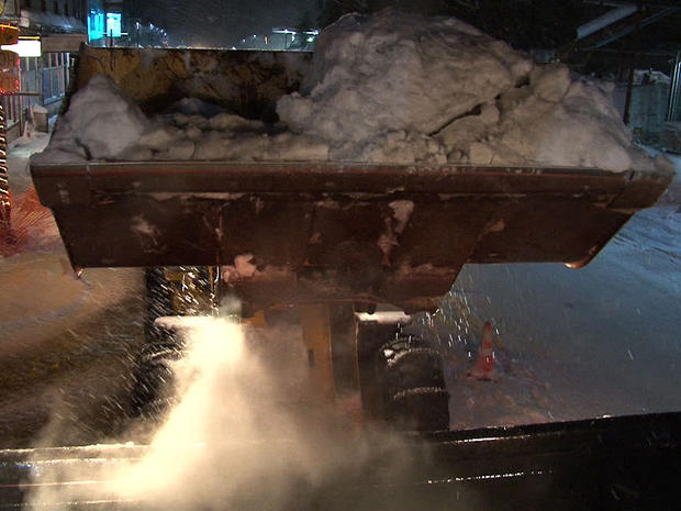 Heavy digging equipment is used to move tons of snow clogging the roads of Cordova