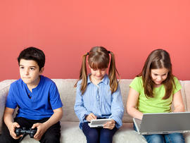 Three children using video games and laptop.