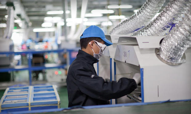 A worker at an Apple supplier facility in Chengdu, China, uses a laser etching machine.