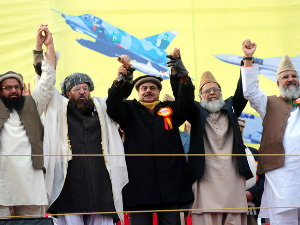 Pakistani Islamist and political party leaders, from left to right Hafiz Muhammad Saeed, Maulana Sami ul Haq, Hamid Gul, Syed Munawar Hasan and Muhammad Ahmed Ludhianvi, raise hands in solidarity at a Pakistan Defense Council rally in Rawalpindi, Pakistan, Jan. 22, 2012.