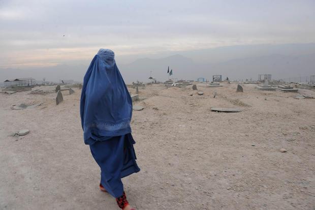 A burqa-clad Afghan woman walks in a cemetery Kabul on November 23, 2011.
