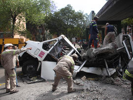 Firefighters work to remove a cement beam that fell from a bridge onto a public bus after an earthquake was felt in Mexico City Tuesday March 20, 2012. A strong 7.4-magnitude earthquake hit central and southern Mexico on Tuesday, collapsing at least 60 homes near the epicenter and a pedestrian bridge in the capital where people fled shaking office buildings in fear. There were no passengers in the mini-bus and the driver suffered minor injuries, according to firefighters.