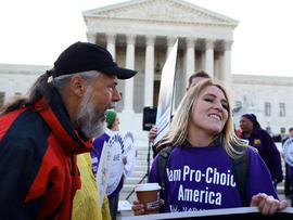 Richard Mondale yells at a Obama health care reform supporter during a protest in front of the U.S. Supreme Court building March 27, 2012, in Washington.