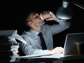 Manager working in office at night and drinking coffee at his workplace