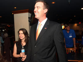 Republican Jesse Kelly, center, smiles as he waits for special election primary results for southern Arizona's 8th Congressional District with his wife, Aubrey Kelly, at the Viscount Suite Hotel in Tucson, Ariz., April 17, 2012.