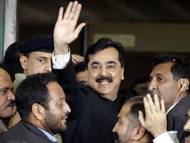 Pakistani Prime Minister Yousuf Raza Gilani, center, waves upon his arrival at the Supreme Court for a hearing in Islamabad, Pakistan, April 26, 2012.