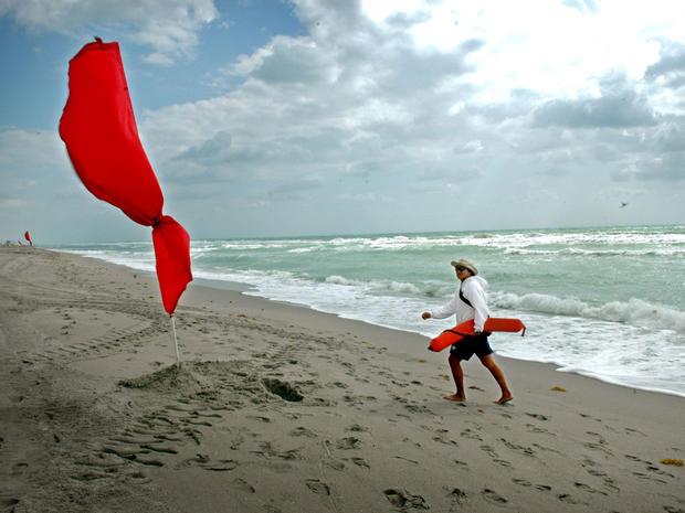 在刮风的日子,救生员在佛罗里达的Hallandale海滩走。