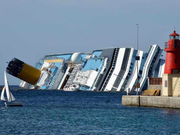 A small dinghy sails past the stranded Costa Concordia cruise ship near the harbor of Giglio Porto June 25, 2012, in Italy.