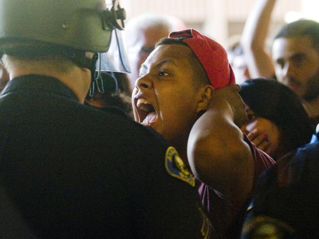 一名抗议者尖叫着警察挡住阿纳海姆市议会分庭的门口
