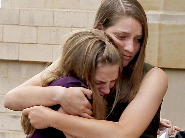 2012年7月25日星期三,他们在丹佛举行的戈登考登纪念仪式上为哀悼者互相保持联系。