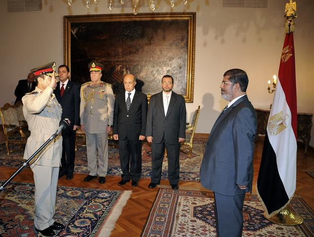Egyptian President Mohammed Morsi, right, swears in newly-appointed Minister of Defense, Lt. Gen. Abdel-Fattah el-Sissi, left, in Cairo, Egypt, Sunday, Aug. 12, 2012.