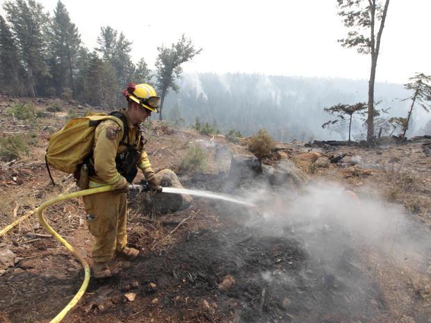 2012年8月20日星期一,消防队员Josh Gillick在加利福尼亚州维奥拉附近的Ponderosa火灾热点地区消防。超过1,400名消防员正在与摧毁七座房屋的火灾作斗争,烧毁了23平方英里。