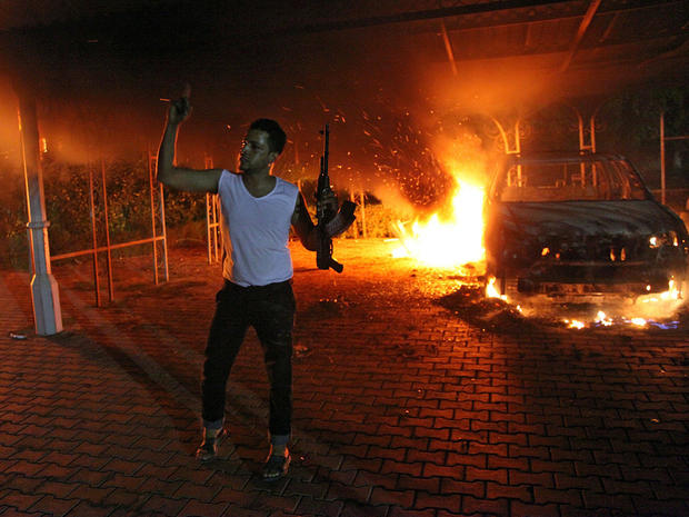 A man waves his rifle as buildings and cars burn after being set on fire inside the U.S. consulate compound in Benghazi