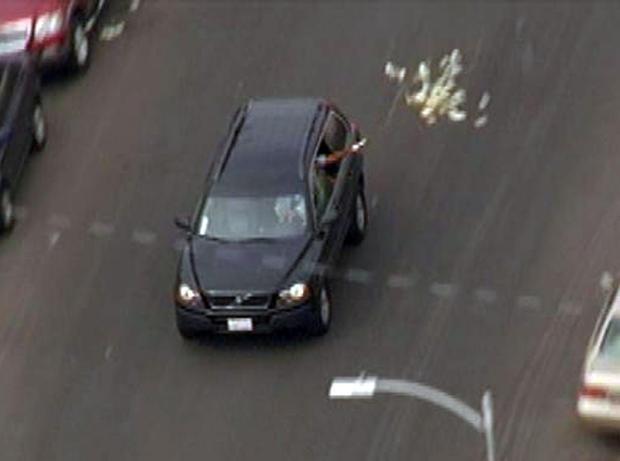 银行抢劫嫌疑人向SUV投掷现金,因为它正在被警长的代表通过洛杉矶街道周三追逐