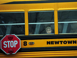 A child looks out of a bus window as it passes by St. Rose of Lima Catholic Church, where the funeral of James Mattioli, 6, was taking place Dec. 18, 2012, in Newtown, Conn.