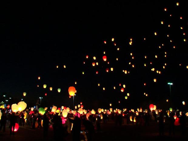 一群人聚集在一起,释放中国的灯笼,庆祝杰登的九岁生日。