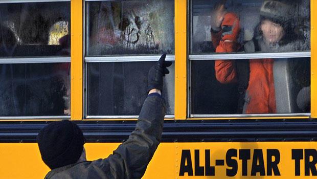 2013年1月2日,星期三,在康涅狄格州新镇,一个男人在假期休息后的第一天上班时在公共汽车上向孩子挥手。