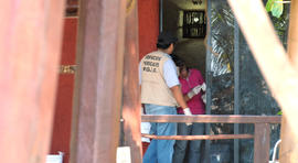 Police investigators work to obtain fingerprints on a door at the home where masked, armed men broke in, in Acapulco, Mexico, Tuesday Feb. 5, 2013. According to the mayor of Acapulco, five masked men burst into this house that Spanish tourists had rented on the outskirts of Acapulco, in a low-key area near the beach, and held a group of six Spanish men and one Mexican woman at gunpoint, while they raped the six Spanish women before dawn on Monday.