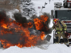 A firefighter places wheelblocks as he prepares to extinguish a vehicle fire in Lawrence, Kan., Feb. 21, 2013. The car caught on fire trying to make it up a snow covered hill.