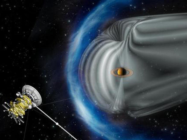 This artist's impression shows NASA's Cassini spacecraft exploring the magnetic environment of Saturn. Saturn's magnetosphere is depicted in grey, while the complex bow shock region â?? the shock wave in the solar wind that surrounds the magnetosphere â?? is shown in blue. The image is not to scale.