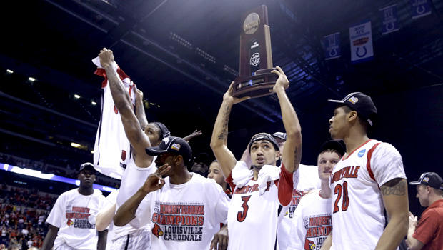 Louisville guard Peyton Siva (3) holds up the regional trophy as Louisville players celebrate their 85-63 win over Duke in the Midwest Regional final in the NCAA college basketball tournament, Sunday, March 31, 2013, in Indianapolis.