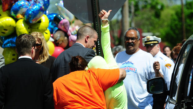 Gina DeJesus raises her thumb as she arrives at her family house on May 8, 2013 in Cleveland, Ohio. DeJesus along with two other women were rescued this week after a decade spent imprisoned and tormented in a kidnapper's house made an emotional return to their families on Wednesday. At right is Gina's father Felix.