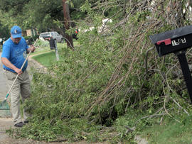Don Graf cleans his property in Cleburne, Texas, May 17, 2013, two days after powerful storms produced 16 tornadoes in the area.