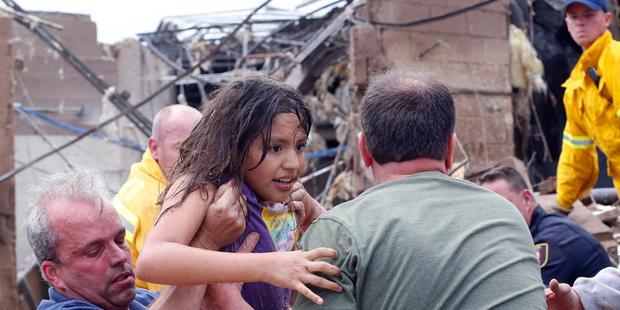 一名儿童从俄克拉荷马州摩尔的Plaza Towers小学的废墟中被拉出来,于2013年5月20日星期一被送往救援人员。龙卷风宽达一英里(1.6公里),风速高达200英里/小时(周一,俄克拉荷马城郊区咆哮着320公里/小时,整个社区变得扁平化,建筑物着火,直接打击小学。