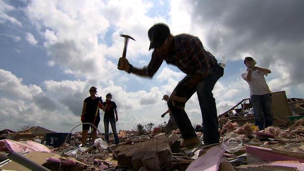 乔·马洛(Joe Mallo)挖掘了位于俄克拉荷马州摩尔(Okore)的一座龙卷风破坏的房子的废墟。
