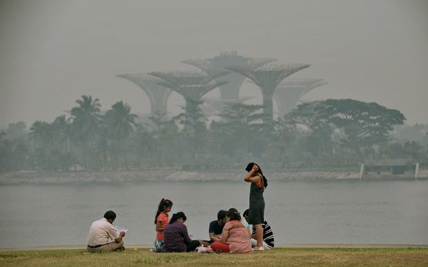A group of people sit along the bay as the Garden by the Bay's Super Trees are shrouded by haze in Singapore