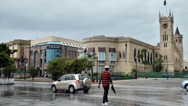 2013年7月9日星期二,当热带风暴尚塔尔接近加勒比海巴巴多斯岛时,一名男子穿过布里奇敦市中心议会大楼前的一条异常空荡荡的街道。