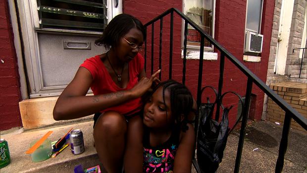 两名巴尔的摩居民坐在一个废弃的房子的门廊上。