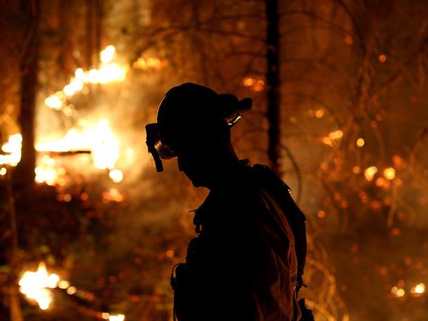 Cosumnes消防局的一名消防员在2013年8月22日在优胜美地国家公园外的加利福尼亚州格罗夫兰市与Rim Fire作战时监视着一场背火。