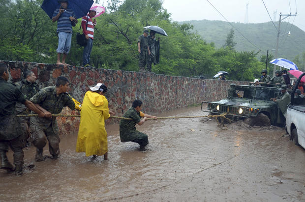 Army soldiers work to try to get their vehicle out of a flooded portion of a road caused by Tropical Storm Manuel in the city of Chilpancingo, Mexico, Sunday Sept. 15, 2013. In the southern Pacific Coast state of Guerrero, rains unleashed by Manuel resulted in the deaths of six people when their SUV lost control on a highway headed for the tourist resort of Acapulco. Another five people died in landslides in Guerrero and Puebla states, while the collapse of a fence killed another person in Acapulco.