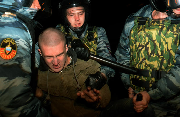 Russian riot police escort a man detained during mass rioting in the southern Biryulyovo district of Moscow