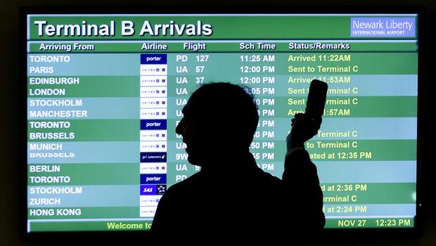 2013年11月27日,在纽约州纽瓦克市,旅行者在感恩节旅行中获得了一个良好的开端,一个人指着显示飞机旅行清单的屏幕,同时他在纽瓦克自由国际机场的电话上讲话。