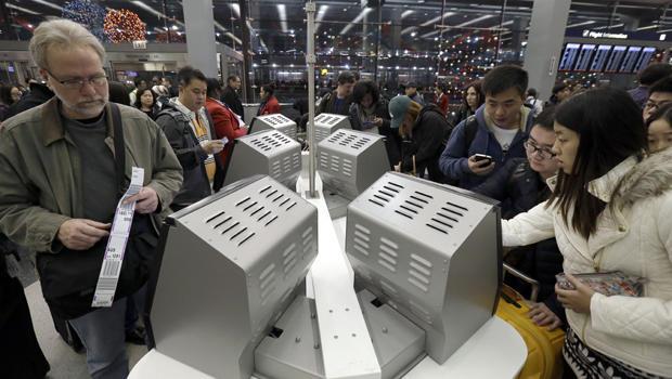 旅行者在2013年12月21日芝加哥奥黑尔国际机场3号航站楼的美国航空公司售票处办理登机手续。
