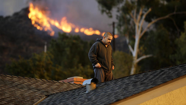 A man walks off a rooftop after spraying water on his home as firefighters battle a wildfire Jan. 16, 2014, in Azusa, Calif.